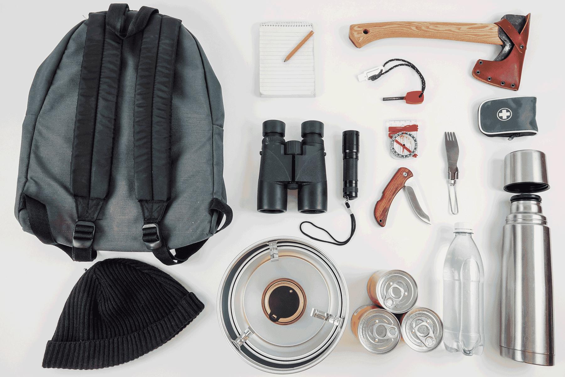 Der übliche Inhalt eines Survival Bug Out Bag: Axt, Feldstecher, Wasser, Kompass etc.