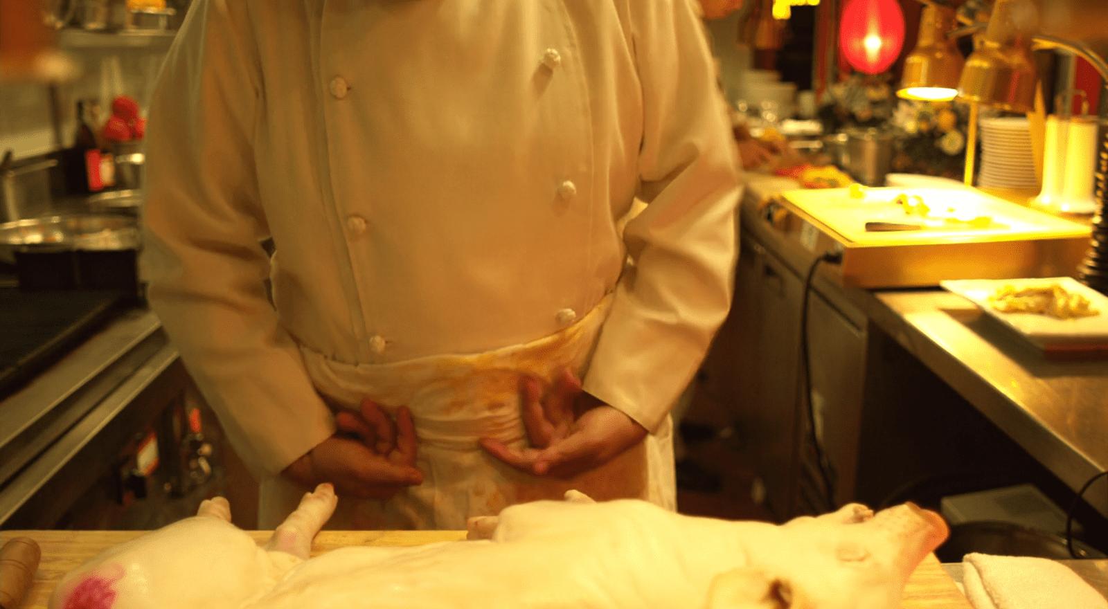 Über den Zwischenwirt Schwein gelangt das Virus an die Hände eines Kochs. Filmstill aus Contagion (Soderbergh 2011).